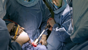 doctors performing hip replacement surgery