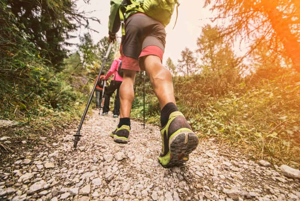 hikers with knee pain walking up mountain